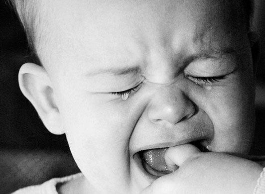 Ребенок сует пальцы в рот при прорезывании зубов